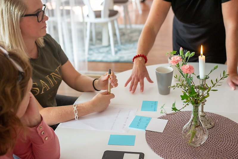 Personer som sitter vid olika bord och har möten/diskussioner
