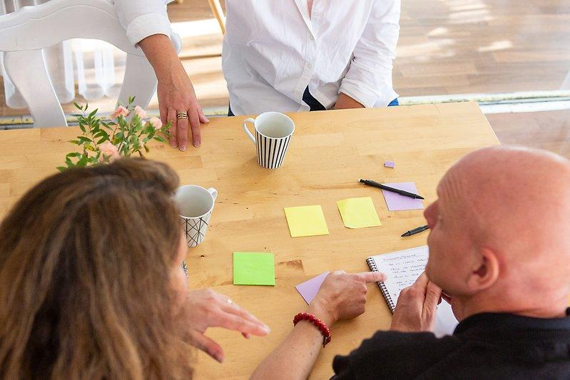 Personer som sitter vid ett bord och har möte